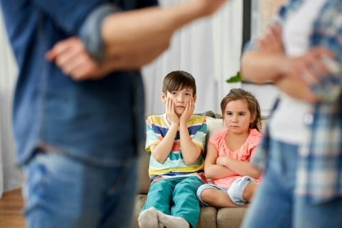 Two parents talking in front of children